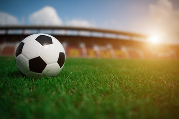 soccer ball on grass with stadium background