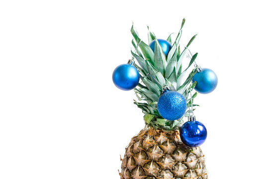 Pineapple top with blue Christmas decorations on white background