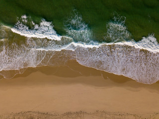 Beach on aerial drone top view with ocean waves reaching shore