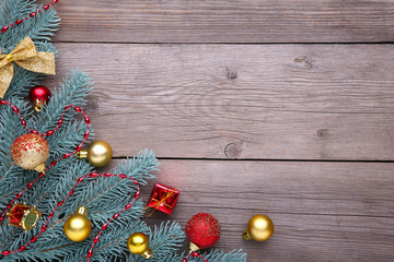 Christmas decoration. Fir-tree branch with balls, gifts and bows on a grey background
