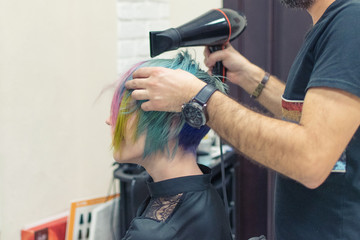 A woman is done coloring her head in blue at the hairdresser's salon. Change the image of a woman.