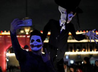 """A man with his face painted as a """"Catrina"""" takes pictures of an art installations of skeletons at a theatre where artists assembled an altar ahead of the Day of the Dead, at Zocalo Square in Mexico City"""