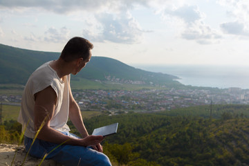 A man with tablet computer on a hill top