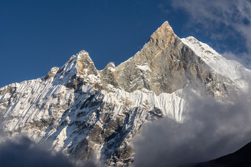 Fish Tail Summit ( also Machapuchare) surrounded by rising clouds in Annapurna range, Himalayas