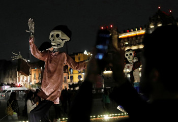 A man takes a picture of art installations of skeletons at a theatre where artists assembled an altar ahead of the Day of the Dead, at Zocalo Square in Mexico City