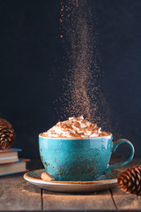 Papiers peints Chocolat Hot chocolate with cream and cinnamon stick in a blue ceramic cup on a table with a books. The concept of winter or fall time.