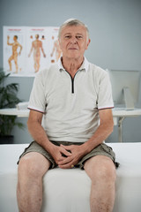 Smiling senior man sitting on bed in office of general practitioner