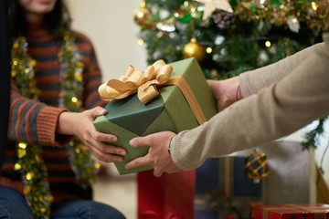 Hands of couple exchanging presents on Christmas eve