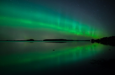 Northern lights dancing over calm lake in Faenebofjarden national park in Sweden