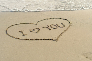 "writing words ""I love you"" on sand of beach"