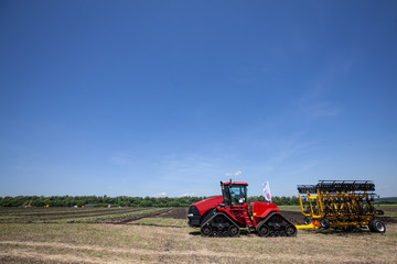 heavy red tractor at agricultural exhibition in motion