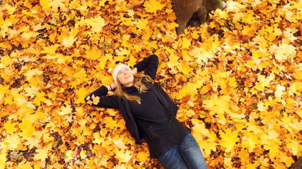 Girl in the autumn forest spends carefree time lying on a carpet of leaves.