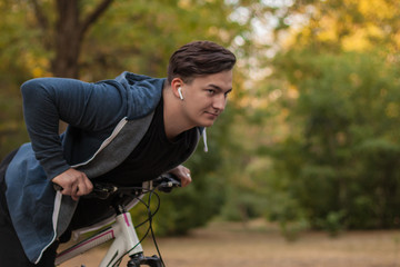 Attractive young caucasian man with dark hair bicycles the park. White earphones/headphones, favorite music. Outdoors, golden leaves. Healthy life concept, sport, fitness. Copy space