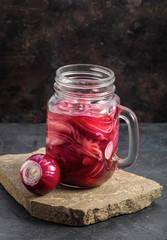 Mason jar of pickled purple onion on stone