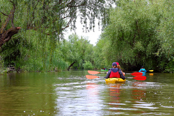 Group of friends travel by kayaks. Kayaking in Danube river and lake on biosphere reserve in spring