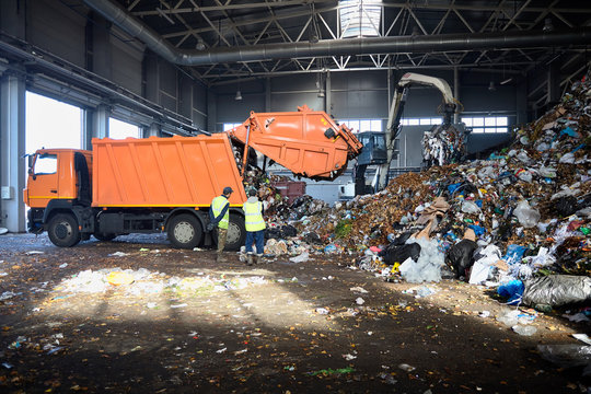 Two workers of recycling plant control process of unloading garbage from garbage truck