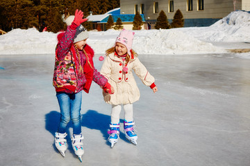 Little girls learn to skate. They are laughing and happy. Concept of friendship and fun holidays.