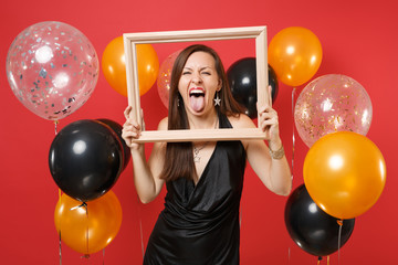 Funny young girl in little black dress celebrating showing tongue holding picture frame on bright red background air balloons. St. Valentine's Day Happy New Year birthday mockup holiday party concept.