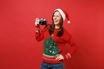 Funny young Santa girl in knitted sweater, Christmas hat blinking hold retro vintage photo camera isolated on red background. Happy New Year 2019 celebration holiday party concept. Mock up copy space.