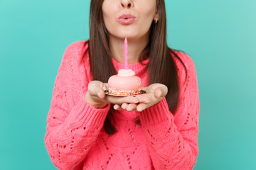 Cropped image of young woman in knitted pink sweater blowing out candle on cake in hands isolated on blue turquoise wall background studio portrait. People lifestyle concept. Mock up copy space.