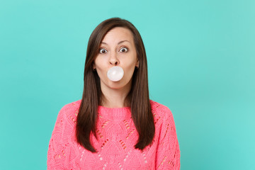 Amazed young woman in knitted pink sweater chewing blowing bubble gum balloon isolated on blue turquoise wall background studio portrait. People sincere emotions lifestyle concept. Mock up copy space.