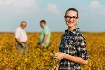 Group of farmers standing in a field examining soybean crop before harvesting. Young female farmer looking at camera. Wall mural
