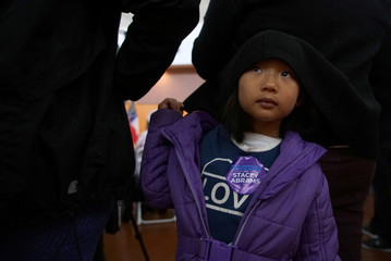 A young girl hides under her father's coat at the Democratic gubernatorial candidate for Georgia, Stacey Abrams, rally ahead of the midterm elections in Riverdale, Georgia