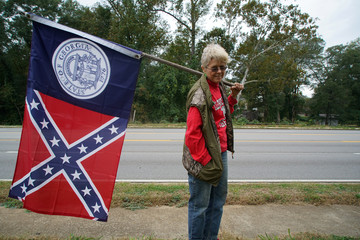 A woman holding a vintage version of the Georgia State Flag alongside a highway