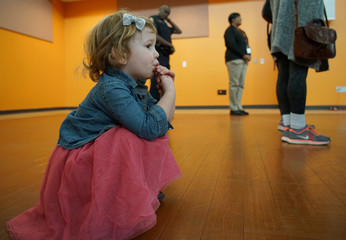A  girl takes a candy break as her mother listens to Stacey Abrams, Democratic gubernatorial candidate for Georgia, in Riverdale, Georgia