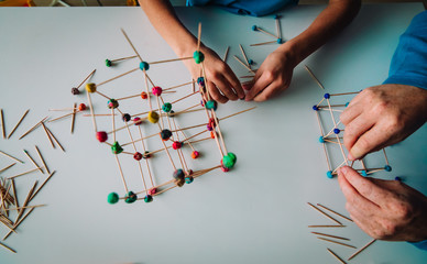 teacher and child making geometric shapes from sticks and play dough