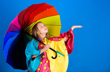 Waterproof accessories for children. Enjoy rainy weather with proper garments. Waterproof accessories make rainy day cheerful and pleasant. Kid girl happy hold colorful umbrella wear waterproof cloak