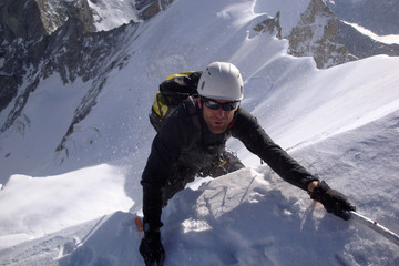 mountain climber reaches the edge of a summit ridge and exits a steep north face in windy and nasty weather in the Swiss Alps