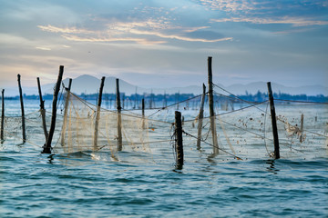 fishing net stretched in the sea at sunset background