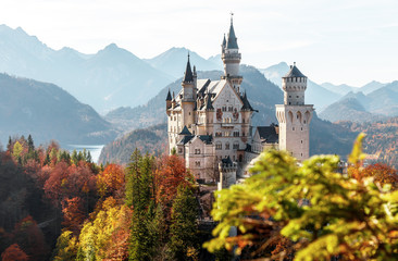 Beautiful view of world-famous Neuschwanstein Castle with Alpine mountains on Background, under sunlit. Wonderful sunny landscape in Alps.   near Fussen, southwest Bavaria, Germany. Fototapete