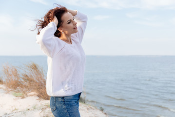 Young woman in warm white sweater on the sea shore.