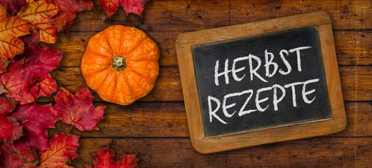 Herbstlaub mit Kürbis auf einem Holzbrett mit Tafel - Herbstrezepte