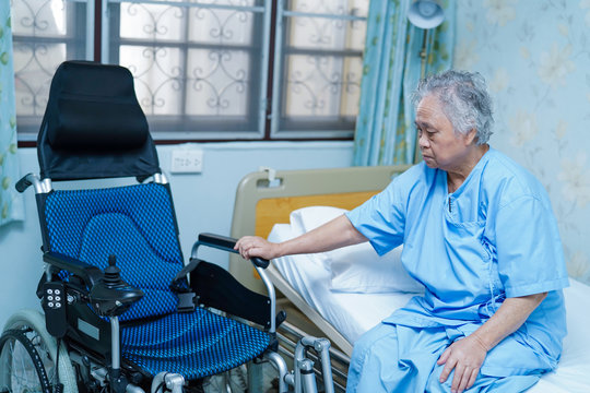 Asian senior or elderly old lady woman patient sitting on bed with wheelchair in nursing hospital ward : healthy strong medical concept