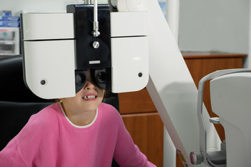 Optometrist examines the sight of little girl at eye clinic
