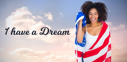 Composite image of pretty girl wrapped in american flag smiling