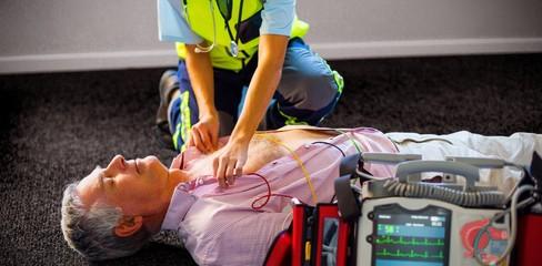 Paramedic using an external defibrillator on an unconscious