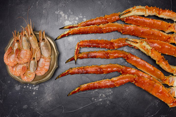King Crab claw with shrimps on black background