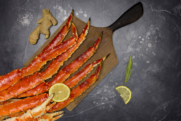 King Crab claw with lemon and ginger at wood board on black background