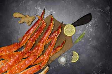 King Crab claw with lemon, salt and ginger at wood board on black background