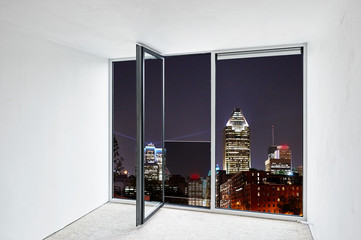 Glass door open in renovated apartment and view on night city lights