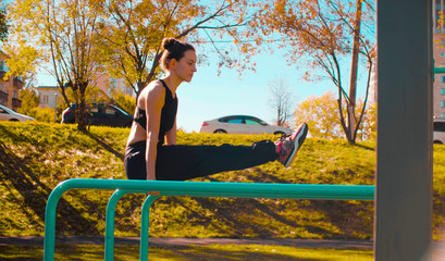 Foto auf Leinwand Gymnastik Young attractive woman doing exercises on parallel bars outdoors. Sunny day, golden autumn