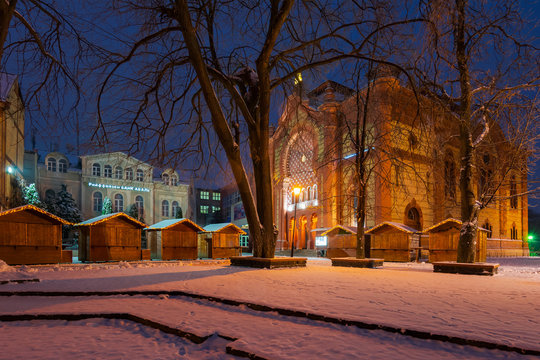 Uzhgorod, Ukraine - DEC 26, 2016: Feczik Park in winter at dawn. former building of synagogue is a popular tourist attraction. location for Christmas fair in town