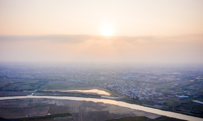 Sunset of fields with various types of agriculture and villages beside with air pollution in winter, Tainan, Taiwan, aerial view