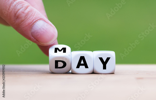 """Hand is turning a dice and changes the word """"may"""" to """"day"""""""