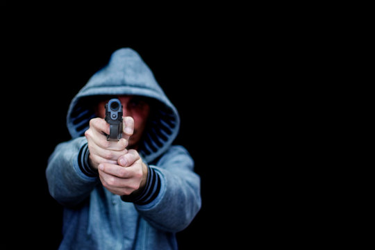 A man aims from a pistol. Isolated on a black background. The concept of threat, danger, defense