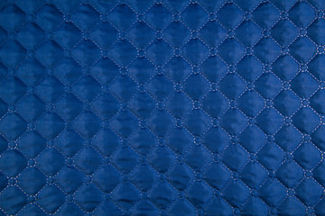 Blue quilted fabric. The texture of the blanket.